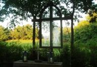 Inmitten von Eichen ist das Altarfenster der Baumkirche mit davorstehenden Holzkreuz zu sehen.