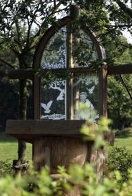 Das Bild zeigt ein freistehendes Altarfenster der Baumkirche auf dem Kolonistenhof. Im Vordergrund steht die Kanzel.