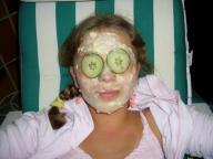 Mädchen mit Quarkmaske und Gurkenscheiben auf den