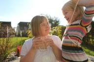 Eine Frau mit Behinderung unterhält sich mit einem Kind. Sie lächeln sich an und trinken Wasser.