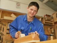 Jugendlicher beim Hobeln in der Holzwerkstatt