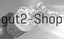 Dies ist die Verlinkung von der Internetseite der Hohenwestedter Werkstatt zum Online-Shop von gut2. Zu lesen ist gut2-Shop. Zu sehen ist in Graustufen eine schräg gehaltene gut2-Flasche.