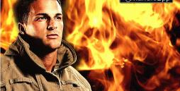 Ein Feuerwehrmann in Einsatzkleidung vor einer Wand aus Feuer