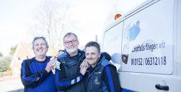 Drei Männer in blauer Arbeitskleidung freundschaftlich aneinander gelehnt neben einem Lieferwagen