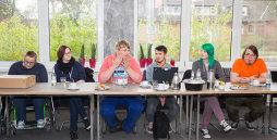 Eine Gruppe von jungen Menschen an Tischen, scheinbar diskutierend