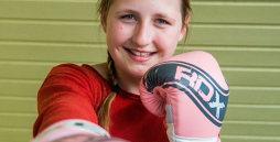 Ein junges Mädchen mit rosafarbenen Boxhandschuhen boxt der Kamera lächelnd entgegen