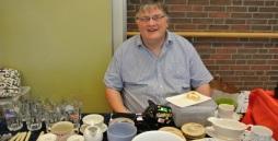 Bild Ein Mitarbeiter mit Handicap sitzt hinter seinem Flohmarktstand