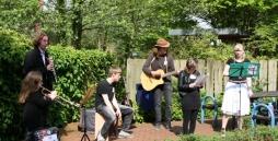 Die Musiker der Band stehen vor dem Freizeithaus und spielen