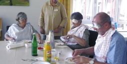Bild: Eine Frau steht an einem Tisch. Drei Menschen sitzen am Tisch. Sie haben Augenbinden auf und frühstücken.