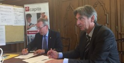 Bild: Zwei Männer in Anzügen sitzen an einem Tisch. Jeder hält einen Stift in der Hand. Sie schreiben auf ein Blatt Papier.
