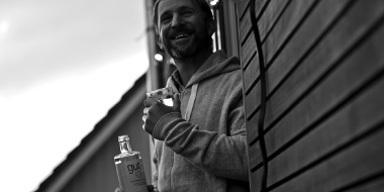 Mann steht an Hauswand, hält Wasser-Flasche in re