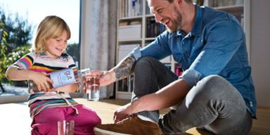 Vater und Tochter sitzen im Haus auf dem Fußboden