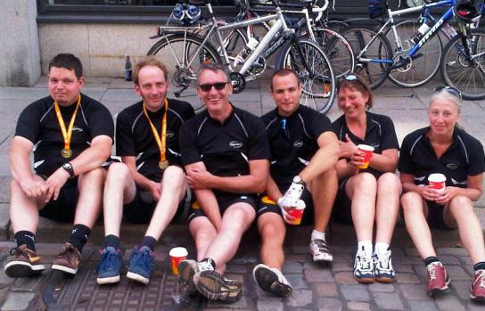 Sechs fröhliche und geschaffte Teilnehmer auf dem Gehweg sitzend nach dem Rennen.
