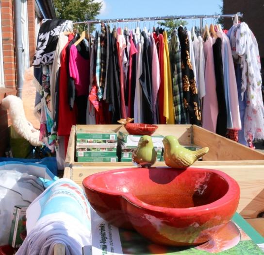 Zum Stöbern: Flohmarktartikel auf Tisch und Kleiderständer