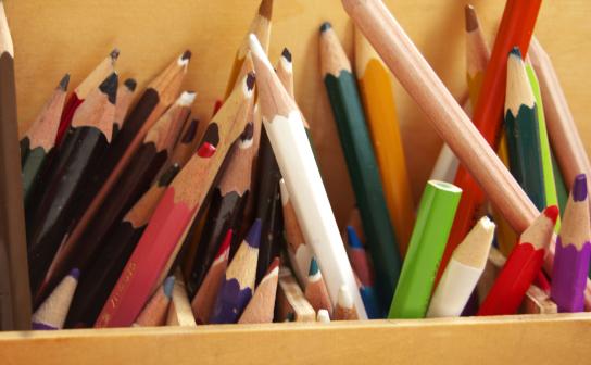 Hier sind viele Buntstifte in einer Holzkiste zu sehen
