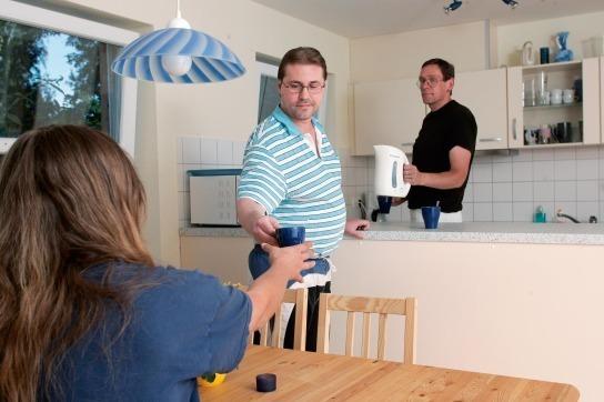 Hier sind 3 Personen in der Küche zu sehen in unserer Trainingswohnung Haus an der Au, Boostedt