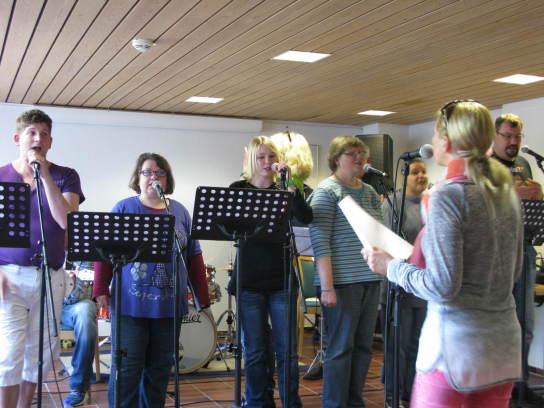 Vier Menschen stehen an Mikrofonen und singen, ang