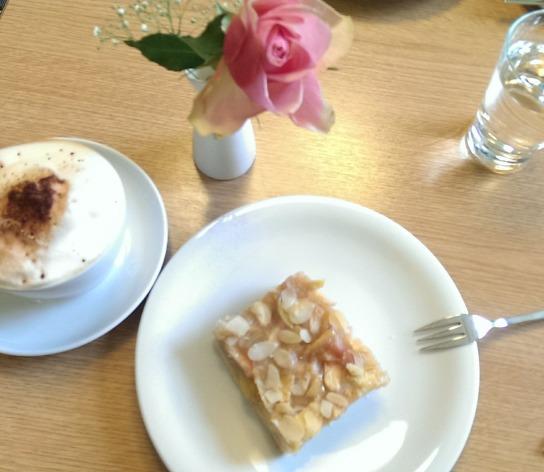 Cappuccino, Apfelkuchen und eine einzelne Rose in