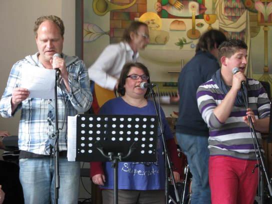Drei Personen stehen an Mikrofonständern und sing