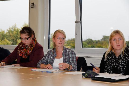 Drei Studentinnen sehen nach vorn, um dem Redner z