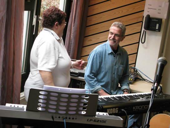 Ein Mann und eine Frau hinter zwei Keyboards lache
