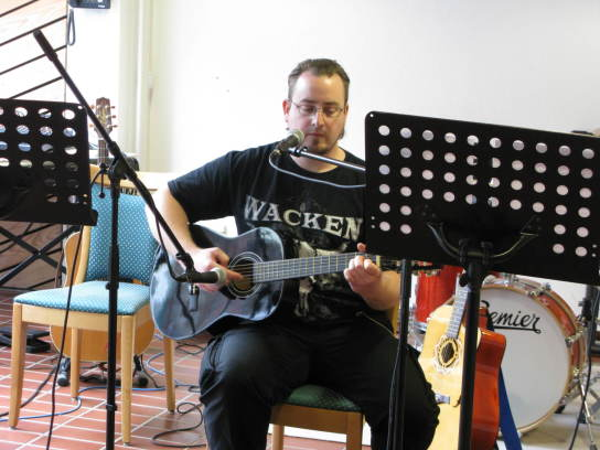 Ein Mann in schwarzem T-Shirt spielt Gitarre und s