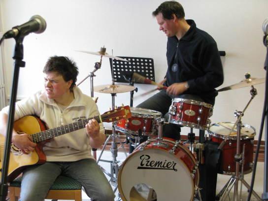 Eine Frau spielt intensiv Gitarre, im Hintergrund