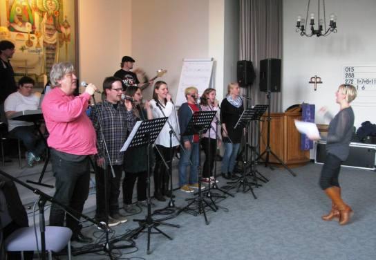 Eine Gruppe von Menschen singt auf einer Bühne