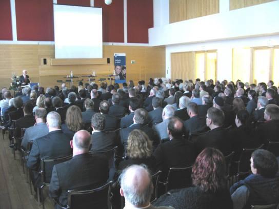 Ein großer Saal voller Menschen, im Hintergrund e