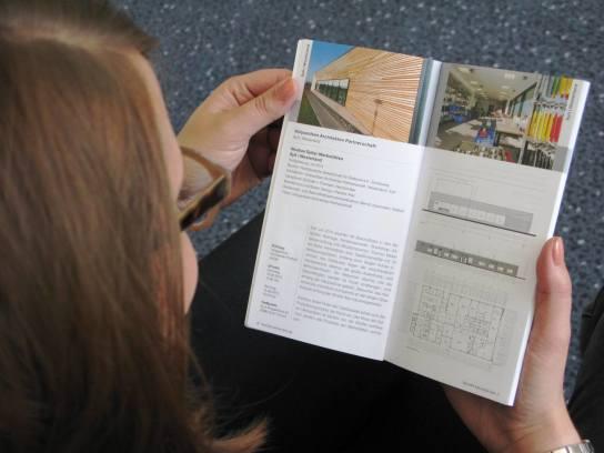 Eine Frauenhand hält eine Broschüre, abgebildet