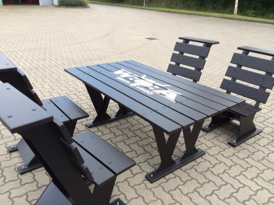 Auf einem Parkplatz stehen schwarze Gartenmöbel a