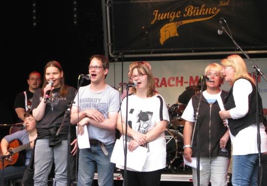 Eine Gruppe von Menschen auf einer Bühne hinter Mikrophonen stehend