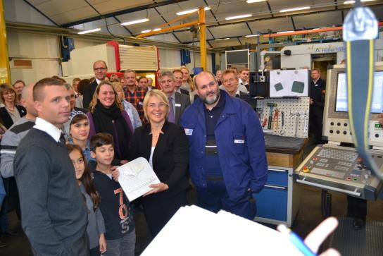 Foto: Die Sozialministerin hält das Ginkoblatt und steht inmitten von Menschen, im Hintergrund Maschinen