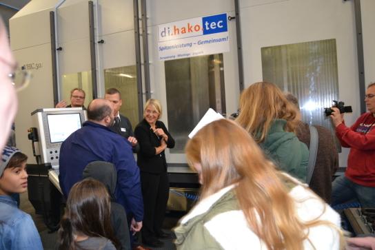 Menschen in einer Halle, die zur Sozialministerin und einer Maschine im Hintergrund blicken