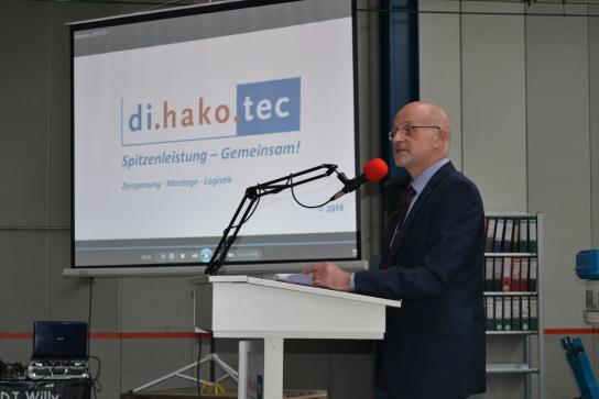 Der Geschäftsführer von di.hako.tec steht an einem Pult mit Mikrophon und spricht, im Hintergrund ist eine Leinwand mit einer Präsentation, auf der das Logo von di.hako.tec zu sehen ist