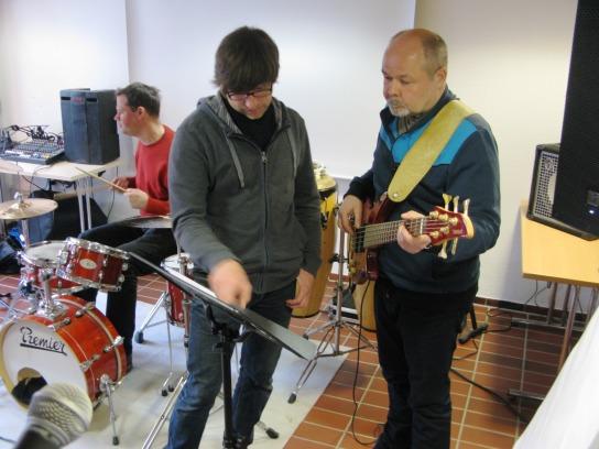 Ein Mann zeigt einem anderen Mann mit Gitarre die richtige Stelle auf einem Notenblatt
