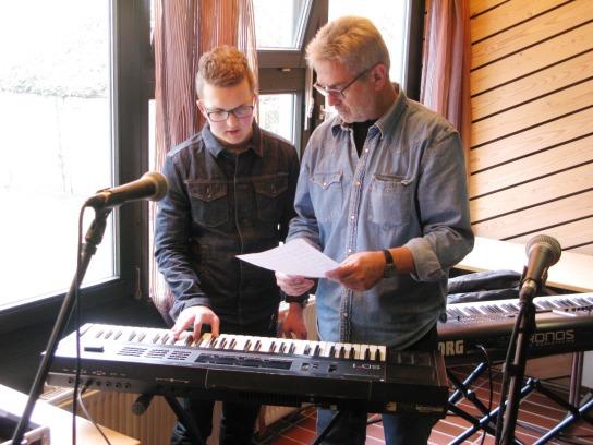 Ein junger und ein älterer Mann stehen gemeinsam am Keyboard