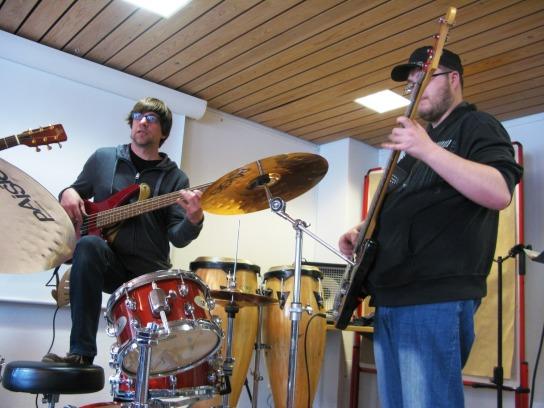 Zwei Männer spielen Bass und Gitarre in einem Probenraum