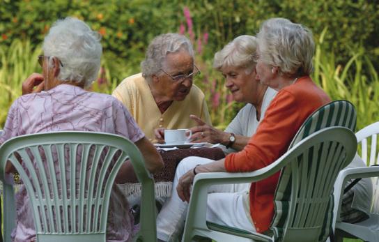 Vier alte Damen sitzen im Garten und trinken Kaffee