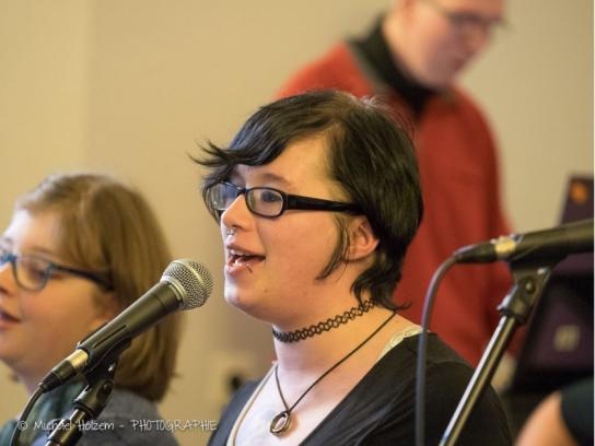 Junge Frau singt in ein Mikrofon