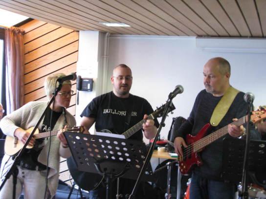 Frau an Ukulele, Mann an Gitarre und älterer Mann am Bass