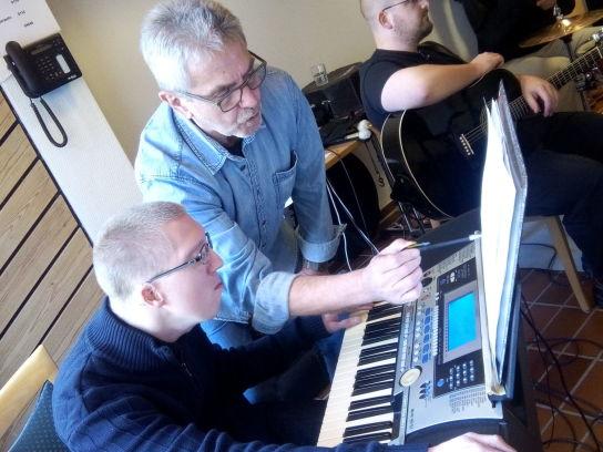 Älterer Mann zeigt jüngerem Mann am Keyboard Noten