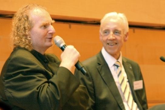 Zwei Männer, einer mit Mikrofon in der Hand, der andere hört ihm zu
