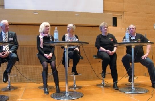 Fünf Menschen auf Barhockern auf einer Bühne, in der Mitte drei Frauen, jeweils außen ein Mann