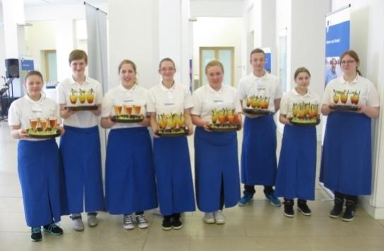 Ein Gruppe von jungen Menschen mit einheitlichen Poloshirts und Schürzen mit Tabletts, auf denen bunte Getränke stehen