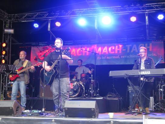 Vier Männer mit Instrumenten auf einer Bühne