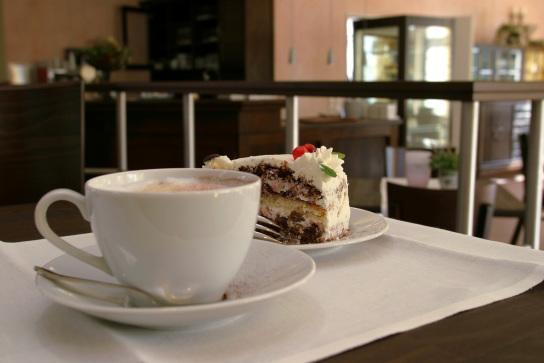 Bild: Eine Tasse mit Kaffee steht vor einem Stück Torte.
