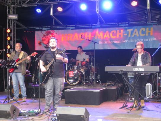 Bild: Vier Männer stehen mit Instrumenten auf einer Bühne.