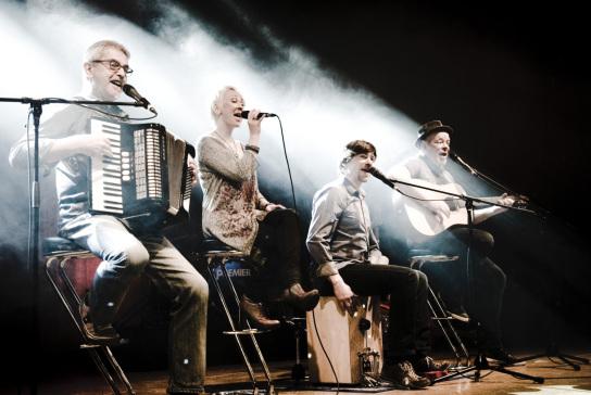 Bild: Drei Männer und eine Frau sitzen auf einer Bühne. Sie spielen Instrumente.