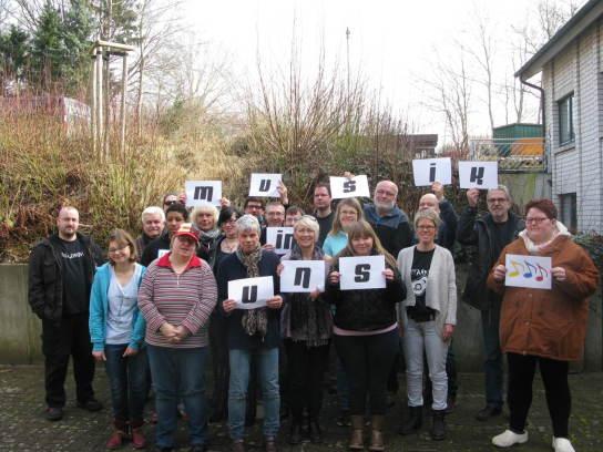 Bild: Eine Gruppe Menschen steht dicht beieinander. Sie lächeln in die Kamera und halten einen Buchstaben in die Luft